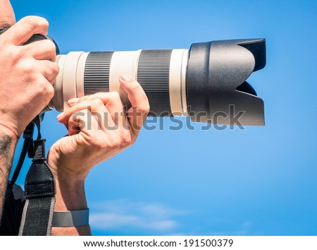 Photographer outdoors with big zoom digital lens as professional equipment getting ready to shoot a photo - stock photo