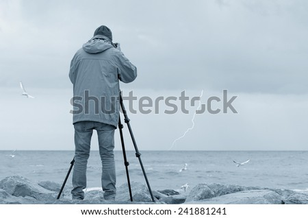 photographer over the cliff with stormy sea - stock photo