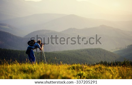 photographer photographed mountains in summer, photographs fog. - stock photo