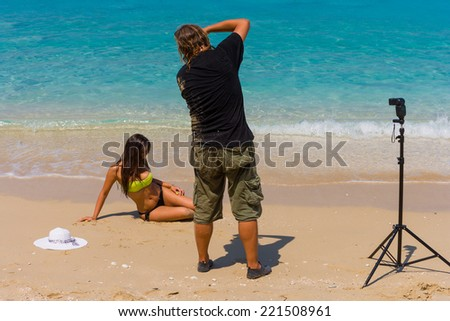 Photographer Photoshoot on the beach with beautiful bikini model - stock photo