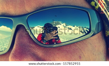 Photographer reflected on sunglasses while climbing Mönch mountain in the Alps, Switzerland - stock photo