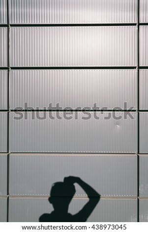photographer's silhouette on the aluminum cladding of the building - stock photo