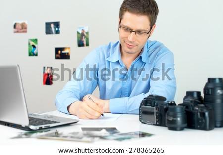 Photographer selecting photos on his computer. - stock photo