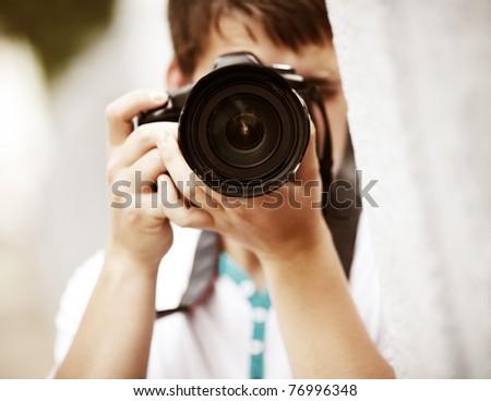 Photographer, selective focus point on nearest part of lens - stock photo
