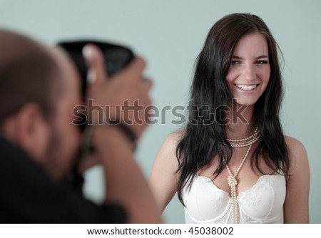 Photographer shooting a female photo model in a studio - stock photo