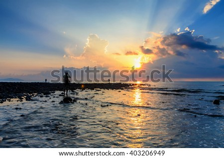 Photographer shooting awesome sunrise with marvelous clouds at Black Stone Beach, Kuantan, Malaysia. Ray of light is visible with reflective black stones on the foreground. - stock photo