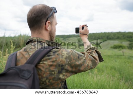 Photographer shooting field with compact camera outdoor