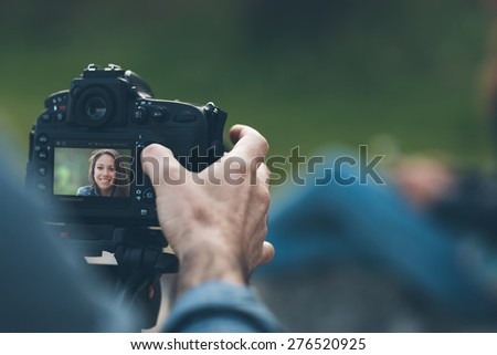 Photographer shooting hands close up and model posing on background - stock photo