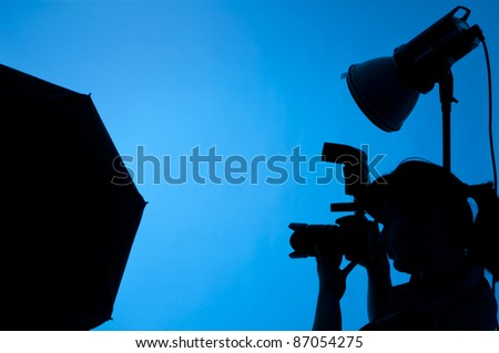 Photographer shooting in studio on a blue background