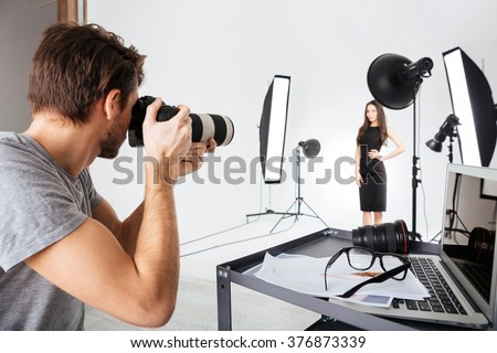 Photographer shooting model in studio with softboxes - stock photo