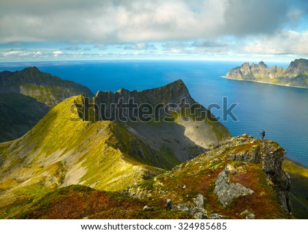 Photographer shooting northern Norway mountains - stock photo