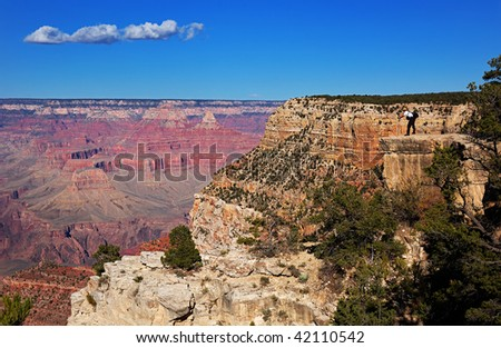 Photographer shooting the Grand Canyon at the edge of the south rim, Arizona - stock photo
