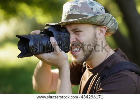 Photographer shooting with DSLR camera in forest - stock photo