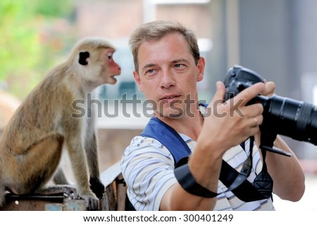 Photographer shows a monkey by her photo shoot - stock photo