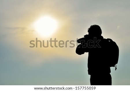 Photographer silhouette shooting near the beach when sun rising