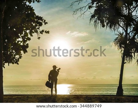 Photographer silhouette shooting sea outdoors on the beach at sunset sky with sun set background. Woman hold in hand backpack, stand under tropical  palm tree leaves against water texture - stock photo
