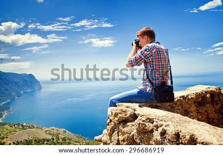 Photographer sits on top of a mountain and taking pictures - stock photo