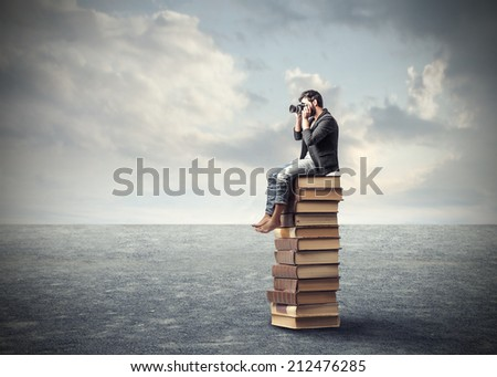 photographer sitting on a pile while taking a picture - stock photo