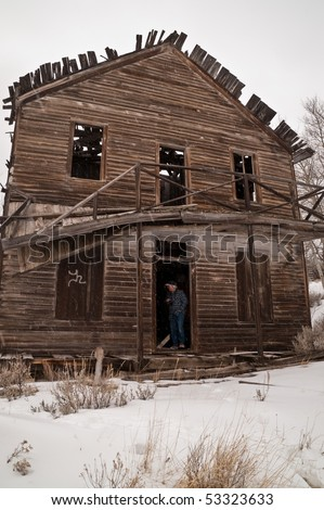Photographer standing in the doorway of the Daily Hotel in Comet, Montana, trying to decide if he dares to go any further to get the shot he wants - stock photo