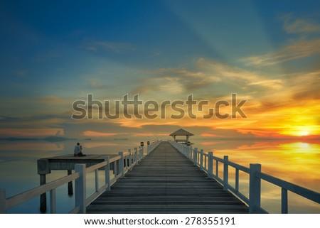 photographer take landscape photo with wooded bridge and sunset - stock photo