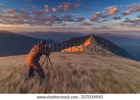 photographer take photo on mountain - stock photo