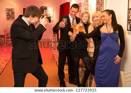 Photographer takes a photo of a group of people celebrating using a DSLR - stock photo