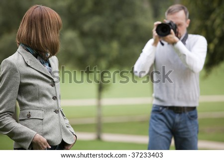 photographer takes a picture from woman outdoors