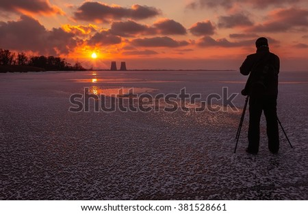 photographer takes a picture of fantastic sunset on a frozen lake - stock photo