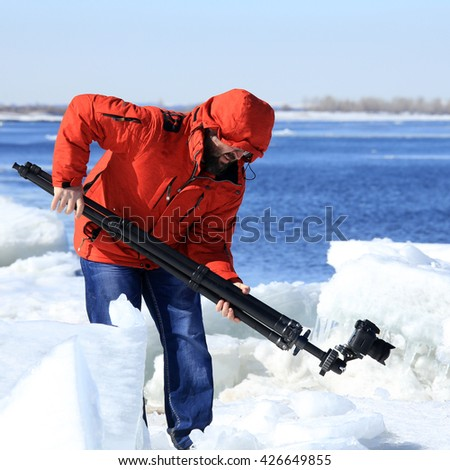 photographer takes the ice on the river in a flood in early spring on a sunny day - stock photo