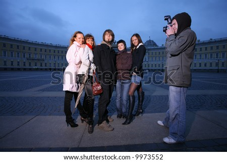 Photographer taking a fashion photo of a small group of young people. - stock photo