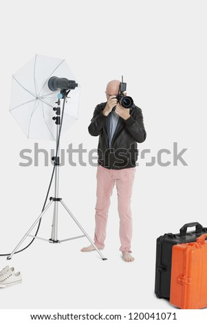 Photographer taking a photograph in studio - stock photo