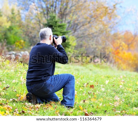 Photographer taking a picture of the beautiful fall scenery - stock photo