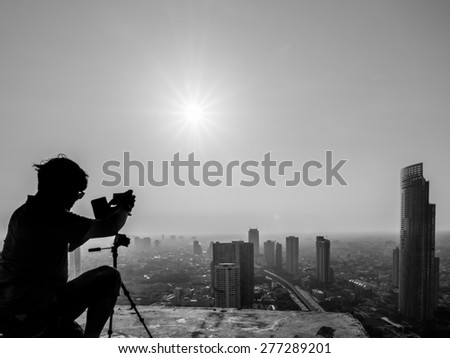 Photographer taking photo on building rooftop, Bangkok Ghost Tower, Thailand - stock photo
