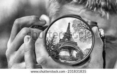Photographer taking photo with DSLR camera at Eiffel Tower. Shallow DOF - stock photo