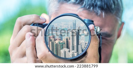 Photographer taking photo with DSLR camera at Hong Kong buildings. Shallow DOF - stock photo