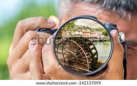 Photographer taking photo with DSLR camera at landscape in Provence. Shallow DOF - stock photo