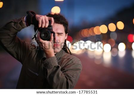 Photographer taking photo with DSLR camera at night. Shallow DOF. - stock photo