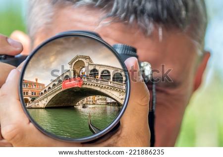 Photographer taking photo with DSLR camera at Rialto Bridge. Shallow DOF - stock photo