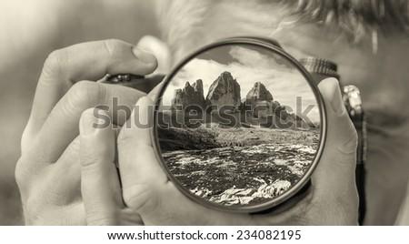Photographer taking photo with DSLR camera at Tre Cime di Lavaredo, Italy. Shallow DOF - stock photo