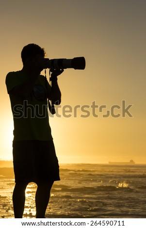 Photographer taking photographs of birds at sunset - stock photo