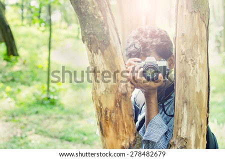 Photographer taking photos framing in between tree trunks with Film camera in natural outdoor, vintage look - stock photo