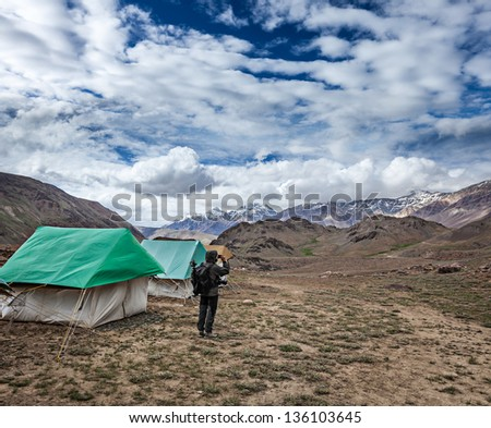 Photographer taking photos in Himalayas mountains with mobile phone. Spiti valley, Himachal Pradesh, India - stock photo