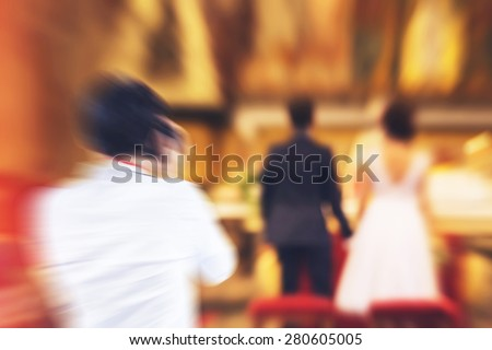 Photographer taking photos of young couple getting married in christian church - religious wedding - radial zoom blur applied, defocused, with instagram filter  - stock photo
