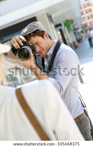 Photographer taking picture of woman model - stock photo