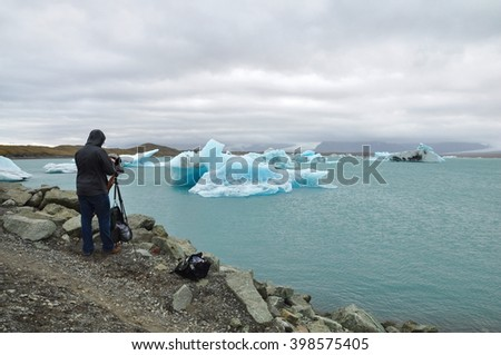 Photographer taking picture with old vintage camera. Icebergs in glacier lake, Jokulsarlon lagoon - Iceland.