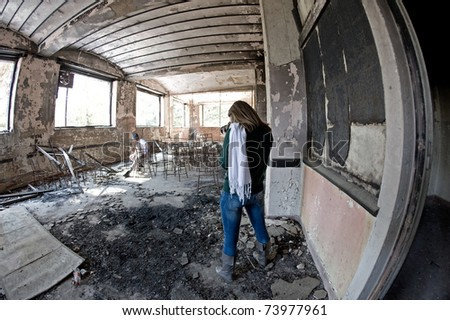 Photographer taking pictures inside abandoned building. - stock photo