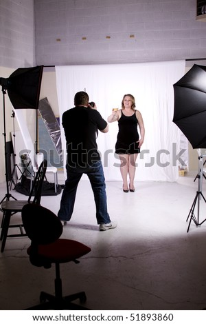 Photographer Taking Pictures of a Model in the Studio