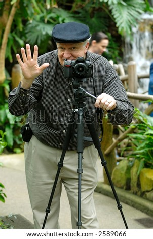 Photographer taking pictures using a tripod. - stock photo