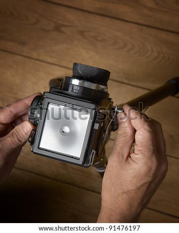 Photographer using a middle format photo camera with tripod on wooden floor - stock photo
