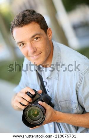 Photographer using reflex camera outside - stock photo